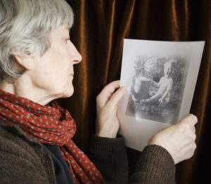 A senior woman looking at old family photos.